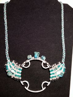 "22 1/2"" kumihimo and macrame nylon white, teal, silver and black cord. Aluminum metal 2 1/2 disc center. SN46 $40"