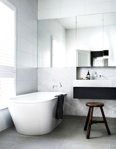 White and marble bathroom with large mirror and wood stool