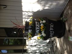 Black flower pots with a message written on them and mums planted inside for the centerpiece