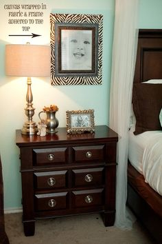 Great idea! Canvas wrapped in fabric.  Frame placed on top.