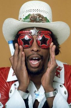 "Bootsy Collins (born William Earl Collins), American funk bassist, singer, & songwriter. Rising to prominence with James Brown (in the J.B.'s) in the late 60s, and with Parliament-Funkadelic in the '70s, his driving bass guitar & humorous vocals established him as one of the leading names in funk.  His signature instrument is a custom-built star-shaped bass guitar he calls the ""Space Bass."" He is a member of the Rock and Roll HoF, inducted with 15 other members of Parliament-Funkadelic."
