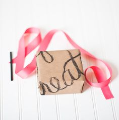 Hand Font: Lettered Wrapping Paper. All you need is a large piece of butcher paper, white craft paper, or in a pinch – a paper grocery bag! Using a chalk pencil will the give the paper an impressionist look, and a final spritz of hair spray will hold it all in place.