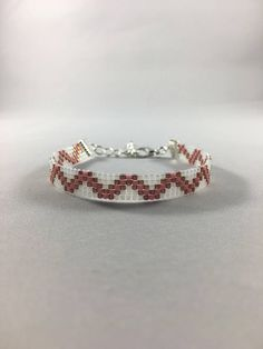 Fun bead loom bracelet in pink and pearlescent white colors. This beautiful bracelet is made with delica beads and finished with a silver ribbon clasps and a two inch extended chain. Can be worn alone or stacked with other bracelets. If you need something larger or smaller or would