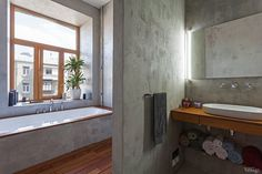 Bedroom, Modern Concrete Bathroom With Large Window Woden Floor White Modern Bathtub And Large Mirror Single Towel Rail Wooden Wall Washstand With White Washbasin Also Colourful Towels: Cool Studio Apartment Design with Open Concept Appartement Design Studio, Studio Apartment Design, Beautiful Interior Design, Modern Interior Design, Interior Architecture, Interior Office, Modern Bathtub, Modern Sink, Concrete Bathroom