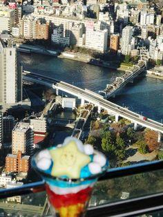 "The limited express ""Ryoumou"" crosses Sumidagawa Bridge as Sorakara-chan Parfait looks down from Sky Tree Cafe."