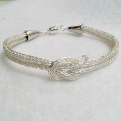 DonnaDStore is away until May 26. All items purchased before May 26 will ship by the 29th.Theres nothing like striking simplicity! This Silver viking knit bracelet is the statement youve been waiting to make! Non-tarnish silver wire has been woven in the double weave technique to create a light yet strong chain, with a Love Knot as the focal and finished with silver bead cones and magnet clasp, making it disability friendly.  The finished piece is just over 8.5 inches long which is a loose…