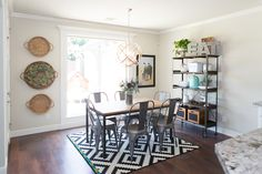 Beautiful dining room from CCandMike.com. Love the bold patterned rug and the basket wall decor!