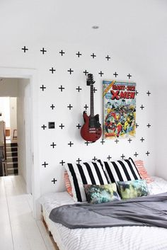 This bedroom proves that almost anything can be wall art: from washi tape crosses or a blown-up comic book cover to a cherished guitar.