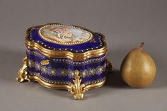 See Info and Many more Images on the Link.. An oval casket with wavy edges in Bresse dark blue enamel with its shell-shaped key and ormolu mounts resting on four curved foliate-scrolled feet. The lid is decorated...