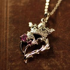 This regal Luckenbooth Thistle Heart necklace has a purple thistle heart design surmounted by the crown of Mary Queen of Scots. The Scotch Thistle is the national flower of Scotland. Mary Queen Of Scots, Art Nouveau, Jewelry Tags, Jewelry Accessories, Scottish Symbols, Celtic Symbols, Princess Cut Diamond Earrings, Thick Gold Chain, Harris Tweed