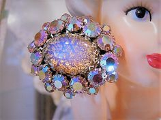 ITEM # 121608  Vintage unsigned Schreiner dragons breath art glass rhinestone brooch with pink aurora borealis rhinestones surrounding the center cabochon. Brooch is circa 1950s-60s. Center cab measures 24mm by 20mm. There are eleven 8mm pink faceted glass rounds with AB finish, and eleven 6mm pink faceted glass rounds with AB finish.  There are many unsigned pieces of Schreiner jewelry because when Schreiner made jewelry for many clothing designers – the Schreiner name tag never went on…