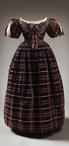 """Queen Victoria's """"Tartan"""" Dress, unknown maker, 1835-37. Scoop neck trimmed with lace; pleats and bows down front, puff elbow-length sleeve, slightly V waist line, unpressed pleated skirt; silk velvet fabric in vertical and horizontal stripes as in tartan. Photo via Vogue UK (see Ann Russell's article, """"Inside Holyroodhouse's New Royal Style Exhibition,"""" dated April 21, 2016). CLICK FOR LARGER IMAGE."""