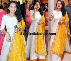 Bhaama in Floor Length Anarkali – Actress Bhaama attended Radhika's wedding wearing a white floor length anarkali teamed with yellow dupatta. Side swept wavy hair and simple jewelry rounded off her look. She looked Indian Fashion Dresses, Indian Gowns Dresses, Dress Indian Style, Indian Designer Outfits, India Fashion, Pakistani Dresses, Asian Fashion, Women's Fashion, Long Gown Dress