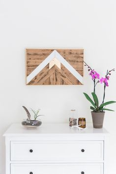 This piece would look amazing hanging on a wall! This reclaimed wood wall art, a mix of earthy materials and contemporary shapes, adds a hint of modern flair to