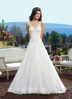 Sincerity wedding dress style 3811 Illusion beaded corded lace A-line gown featuring a V-neckline, a basque  waist and hem lace.The back is finished with a V-back, tulle covered  buttons over the back zipper and a cathedral length train.