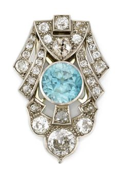 A blue zircon and diamond dress clip circular-cut blue zircon measuring approximately: 9.8 x 9.8 x 5.8mm; central old European-cut diamond weighing approximately: 0.90 carat; remaining diamonds weighing approximately: 2.30 carats total; mounted in platinum.