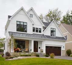 White house with black windows and metal roofline via Summit Signature Homes