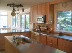 Large, modern kitchen with stainless steel countertops. An island and plenty of counter-top space.