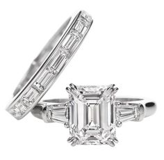 Harry Winston Classic Winston, Emerald-cut Ring. Emerald-cut diamond engagement ring with tapered baguette side stones, featured here in a 2.60 carat center stone, 0.42 carats side stone total weight; platinum setting. Horizontal channel-set baguette diamond wedding band, featured here in total weight 2.35 carats; platinum setting.