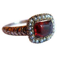c.1820 A rare Georgian ring horizontally set with a faceted red garnet surrounded by seed pearls, the shank decorated with raised flowers, mounted in silver and gold.