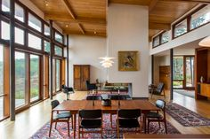 """""""The Finn Juhl teak dining table, Erik Buck teak chairs and Hans Wegner sofa are vintage, while the PH8 Poul Henningsen pendant light and other pieces by Knoll are licensed reproductions of classics. Antique rugs define areas within the large space and warm things up."""""""