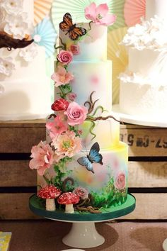 Three-tiered wedding cake with ethereal, hand-painted fondant and lovely sugar paste flowers. Butterflies add the final, serene touches.