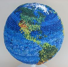 """Artist Julie Kornblum's globe covered in plastic -- that is, crocheted plarn (yarn made from plastic bags) -- definitely makes a colorful statement about """"plastic covering the Earth,"""" doesn't it? Click through to the post for links to tutorials to DIY -- to turn your own plastic bags into yarn, great to use for knitting or crocheting.  #EarthDay"""