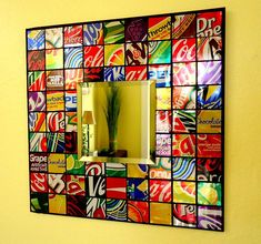 "This funky mirror is made from a variety of soda cans, cut into squares and applied to a black foam board. All cans are flattened, washed and glued in place to resemble a mosaic pattern. Mirror is 3.5"" square beveled design. Entire board is 10"" x 10""."