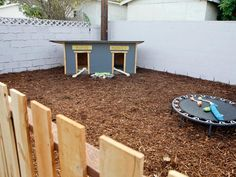 """This fenced-in portion of a backyard featured on Going Yard serves as a dog play area and even has a """"dog duplex"""" doghouse with two doors!"""