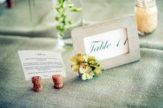 DIY Table numbers: wooden frames, spray painted, glued on flowers, printed numbers. champagne corks used as menu holders