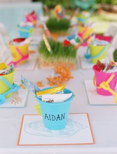 Sand pails filled with treasures for young guests sit at each place setting.