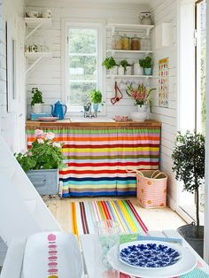 what a lovely white room with bright striped curtains hiding cabinets!