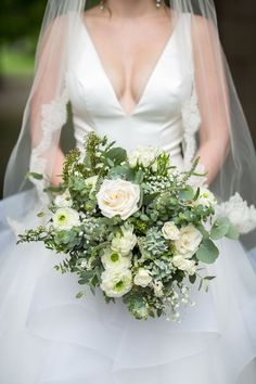 Lush, organic bridal bouquet with lots of texture. White and green wedding bouquet of ivory roses, succulents, white spray roses, white ranunculus, gypsophila, spirea, white veronica, olive and eucalyptus. Florals: Wildflowers LLC Photography: Kristin Van