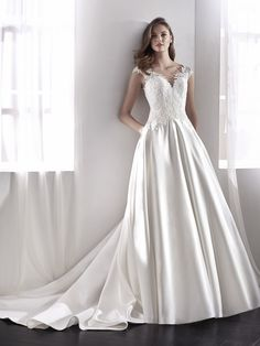 "St. Patrick Bridal l ""LISETE"" l Sensual and modern ballgown wedding dress with side pockets. A full skirt, in satin and with a fitted waist, merges with the bodice and its fabulous Chantilly, thread embroidery and beaded design."