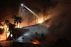 A burning commercial structure at the Poinsettia fire in Carlsbad, California, one of nine wildfires fueled by wind and record temperatures that erupted in San Diego County on May 14, 2014.   Image: David McNew/Getty Images   www.godsfolder.com #GodsFolder