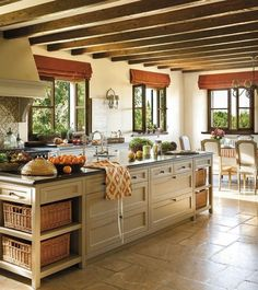 Kitchen - Exposed ceiling beams in a rustic setting with traditional styled large island with lots of storage.   Bang on for styling.