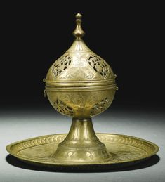 A BRASS INCENSE BURNER, DECCAN, 16TH CENTURY the ovoid body with a domed hinged cover surmounted by a baluster-form finial, decorated with palmettes containing an openwork foliate design separated by engraved floral motifs on a tall, gently splayed foot attached to a circular tray also engraved and punched with foliate palmettes and leafy vines