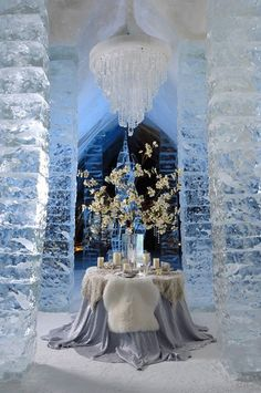 "We love this Disney's ""Frozen"" inspired décor for an adult party! Towering ice pillars, a crystal chandelier, and fur throws all help bring this wintry design together."