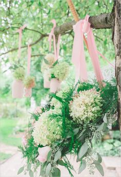 DIY pink painted mason jars with florals hung by pink ribbon. Event Design: Romancing the Stone Styling ---> http://www.weddingchicks.com/2014/05/08/shabby-chic-western-wedding/