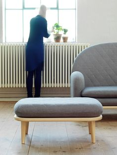 The wooden base of this sofa by Swedish firm Note Design Studio extends outwards to become a side table.
