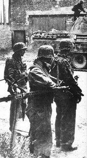 SS-Schütze Günther Streelow avec MG 42, SS-Hauptscharführer Wilhelm Boigk (KIA 04/07/1944) avec des grenades, et avec des jumelles SS-Unterscharführer Wick. Ils sont juste lefting dans la rue où se reposer après l'attaque de Norrey-en-Bessin. 9 Juin 1944.