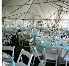 """The Reception Decor    """"We fondly refer to our theme as 'beach elegance,'"""" Jenni says. """"We wanted a natural look that incorporated our beautiful location."""" She and Isaac chose a palette of pale aqua, tan, and ivory, and incorporated subtle seaside touches like raffia and seed pearls throughout the wedding. Beneath the reception tent, large vases filled with sand and shells held up large branches of curly willow and dendrobium orchids."""