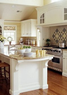 I love the natural light, arched cabinet over the professional stove and the large island. Great soothing colors too~