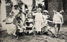 """1920 street carnival Rio de Janeiro  Foliões pertencentes ao Clube de Regatas São Cristóvão, localizado em bairro homônimo, durante o Carnaval, a maioria deles fantasiados de mulheres. Os homens fantasiados de mulheres durante o carnaval são apelidados no Rio de """"cutruvias"""". Rio de Janeiro, fevereiro de 1920."""