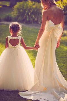 A dress for everyone! We love these dresses with back details; a sweet open heart for the flower girl and a statement bow for the bride! Shop more spring wedding dresses at David's Bridal