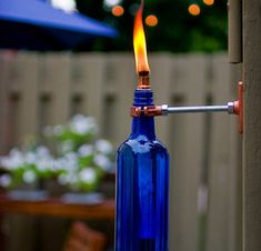 Spruce up your backyard on a budget with these cheap and easy DIY backyard ideas. From patio ideas to landscaping ideas, there are plenty of DIY projects to choose from that are guaranteed to work for big and small yards. Empty Wine Bottles, Wine Bottle Candles, Wine Bottle Crafts, Bottle Art, Glass Bottles, Wine Bottle Tiki Torch, Wall Mounted Vase, Diy Patio, Backyard Patio