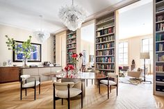 Monumental bookshelves delineate the living and dining areas in the New York home of architect Steven Harris and interior designer Lucien Rees Roberts.