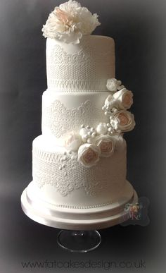 Edible lace wedding cake with soft pastel sugar flowers. Half cascade of flowers with fringed peony on top tier.