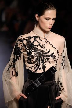 Nude chiffon blouse has full sleeves, stand collar, surplice front with decorative buttons, and an ornate black fauna with bird scene. Zuhair Murad Haute Couture Fall/Winter 2011.