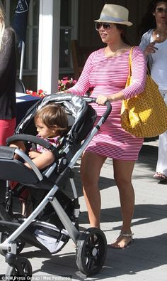 Kourtney Kardashian in a lovely stripey dress showing off her bump!